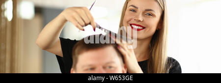 Smiling Hairdresser Combing Hair of Male Client - Stock Photo