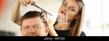 Female Hairdresser Combing Male Client in Salon - Stock Photo