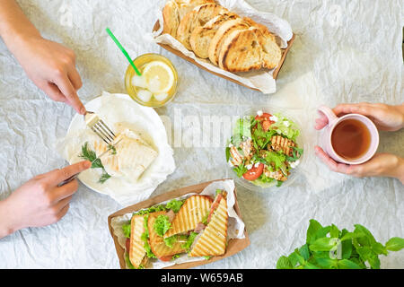 Caesar salad, bruschetta, ham and tomato sandwiches table with hands, top view from above - Stock Photo