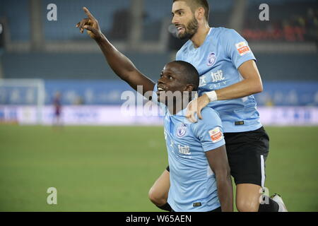Zimbabwean football player Nyasha Mushekwi of Dalian Yifang, lower, celebrates with his teammate Belgian football player Yannick Ferreira Carrasco aft - Stock Photo