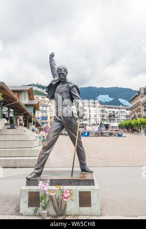 Famous Freddie Mercury statue with flowers on Market Square facing Lake Geneva (lac Leman), Montreux, Vaud, Switzerland - Stock Photo