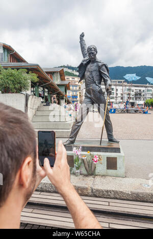 Young man taking photo of famous Freddie Mercury statue on Market Square facing Lake Geneva (lac Leman) in Montreux, Vaud, Switzerland - Stock Photo