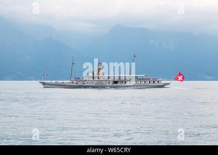 The oldest Belle Epoque restored vintage paddle steamboat Montreux crossing the Lake Geneva (lac Leman) between Switzerland and France with Alps mount - Stock Photo
