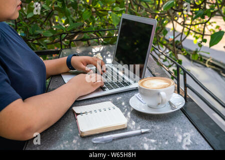 Freelancer using laptop next to notebook and cup of cappuccino - Stock Photo