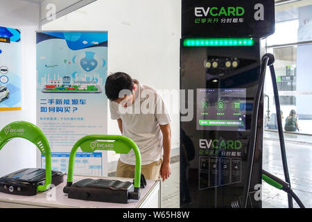 --FILE--A visitor looks at a charging pile for EVCARD shared cars on display during an automobile exhibition for new energy vehicles in Shanghai, Chin - Stock Photo