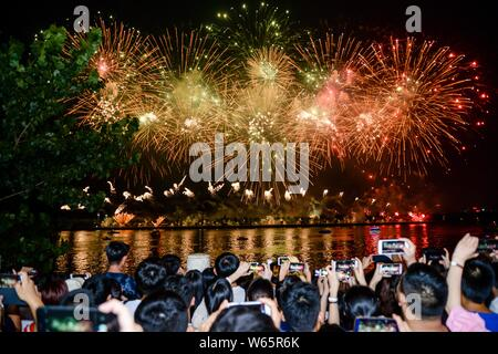 Tourists watch fireworks exploding in the sky over the Xiangjiang River to celebrate the Army Day (August 1) at the Orange Island Park in Changsha cit - Stock Photo