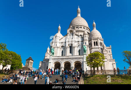 Nice view of tourists at the big staircase in front of the popular landmark Sacré-Cœur Basilica, the famous Roman Catholic church dedicated to the... - Stock Photo