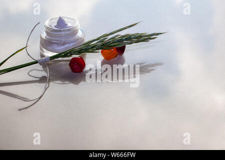 On the reflective surface are three glass, green spikelets and a jar of white cream. Selective focus. The background is blurred. Place for text. - Stock Photo