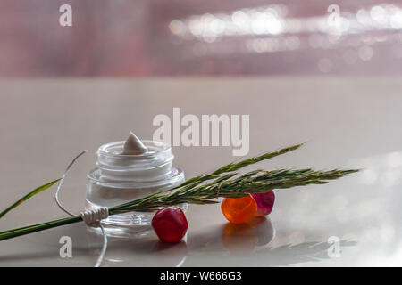 Jar with white cream and spikelets on colored glass pebbles. Spikelets tied with white rope. On the back blurred background glare. Selective focus. Pl - Stock Photo