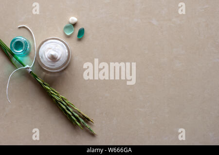 Flat view. Spikelets tied with a white rope, a jar of white cream, a pebble and two glass pieces. Selective focus on the cream. Brown background blurr - Stock Photo