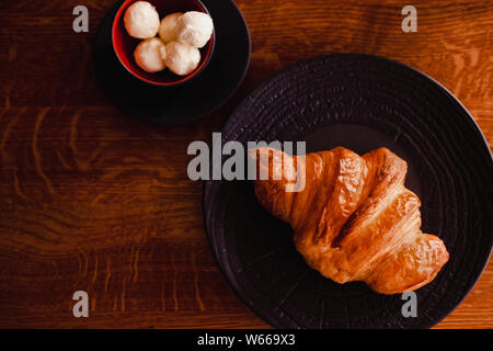 Baked croissant on a black plate with cup of butter on the wooden background. Breacfast bakery restaurant lifestyle. - Stock Photo