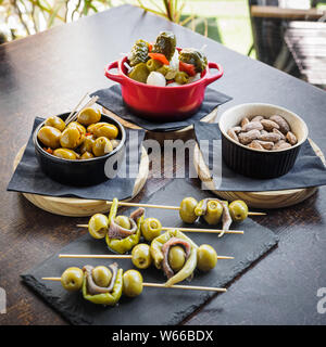 different types of spanish tapas, banderillas, gildas, olives and almonds - Stock Photo