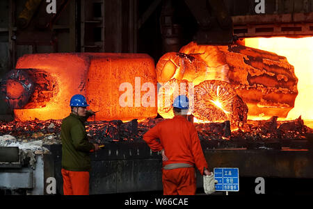 --FILE--Chinese workers survey the production of steel at a plant of Dongbei Special Steel Group Co., Ltd. in Dalian city, northeast China's Liaoning