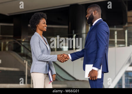 You're hired. Business people shaking hands near office building - Stock Photo