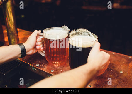 close-up of barman hand at beer tap pouring a draught lager beer. - Stock Photo