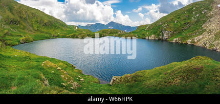 lake capra of romanian fagaras massif panorama. beautiful alpine scenery of carpathians in summer. clouds on the blue sky. grass and boulders on the s - Stock Photo