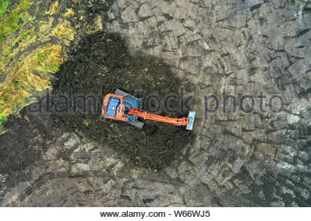 Aerial view of an orange backhoe shifting dirt on a construction site - Stock Photo