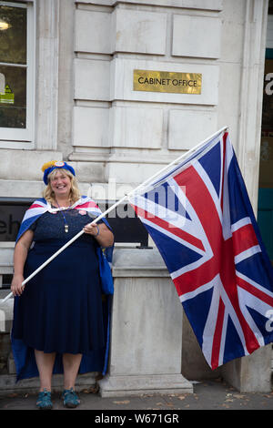 Stop Brexit supporter and remainer with flags protesting outside Cabinet Office on White Hall, London in July. - Stock Photo
