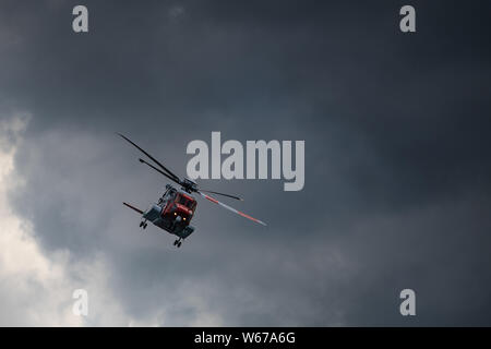 Irish Coast Guard helicopter performing at Bray Air Display 2019 in the open sky. Sikorsky S-92A EI-ICG - Stock Photo