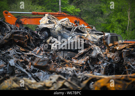 Piles of burnt cars are pictured at a scrap yard in Ammanford, Wales, UK after a fire, leaving twisted and chard metal everywhere. - Stock Photo