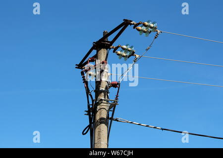 Concrete utility pole with multiple electrical wires connected with ceramic and glass insulators on clear blue sky background - Stock Photo