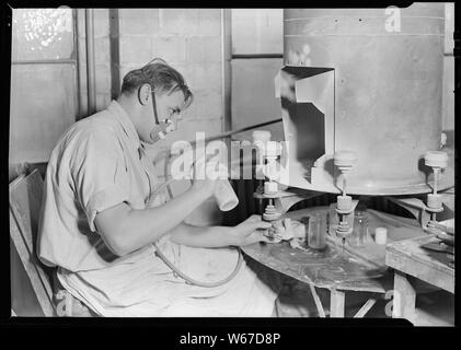Millville, New Jersey - Glass bottles. Paint sprayer, T. C. Wheaton Co. art room. This man is spraying white glass cold cream jars with a hand blowing torch. This is one of the new processes developed by T. C. Wheaton. The jars are put on the forms by a girl who sits at the other side of the machine. They revolve around to this worker who sprays them. The girl then takes the jar off and replaces it with a new one. - Stock Photo