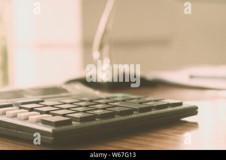 Close up of a calculator placed on office desk. Accounting concept. Vintage background. Isolated. Shallow depth of field. Copy space room for text. - Stock Photo
