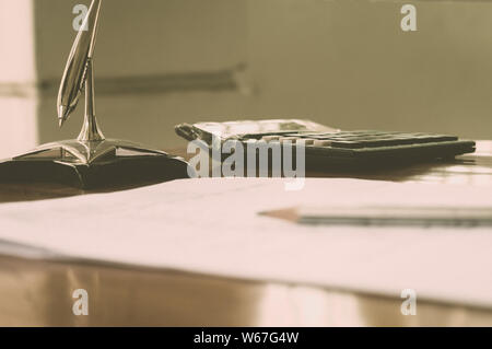 Close up of a calculator placed on office desk. A pen and a paper on the foreground. Accounting concept. Vintage background. Isolated. Shallow deapth - Stock Photo