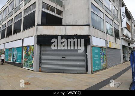 Shutters down over an empt and unused retail outlet on a UK high street. Thousands of shops are closing throughout the UK every week. - Stock Photo