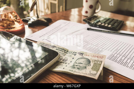 Indian Currency is on the table next to a pen, calculator, money and an application form placed on the desk. Financial Business concept. - Stock Photo