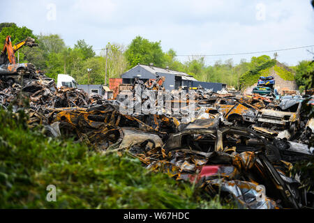 Piles of burnt cars are pictrured at a scrap yard in Ammanford, Wales, UK after a fire, leaving twisted and chard metal everywhere. - Stock Photo