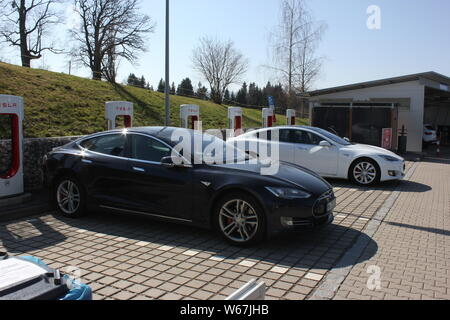Tesla charging station at public charge point, two Tesla cars parking. - Stock Photo