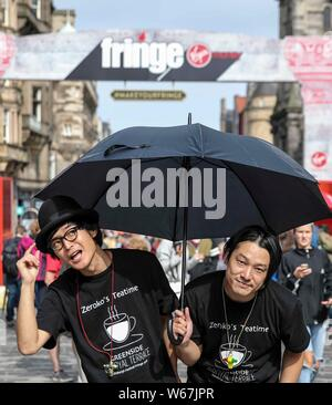 Edinburgh, UK. 31st July, 2019. Previews for the Edinburgh Fringe Festival start with the official start date of 2 August. Performers Zeroko's Teatime hope that the rain will stay away as they perform on the Royal Mile. Credit: Rich Dyson/Alamy Live News - Stock Photo