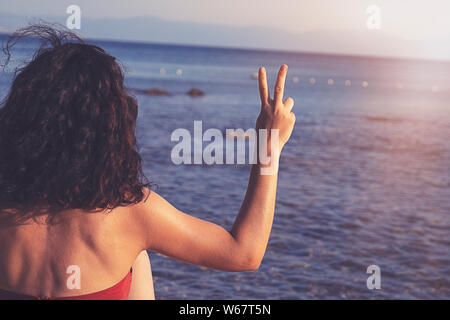 woman holds two fingers or Victory Sign on the beach during sunrise, showing encouragement when we are discouraged. - Stock Photo