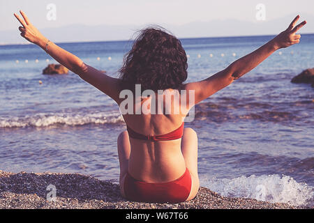 summer vacation, holidays, gesture, travel and people concept - young woman showing peace or victory sign on beach from back - Stock Photo