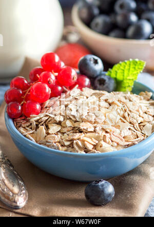 Rolled oats in a blue bowl on a napkin with berries and spoon - Stock Photo