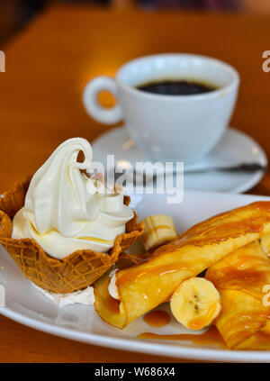 Crepes or pancakes with cream and bananas for breakfast in coffee shop. - Stock Photo