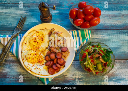 Scrambled eggs with bacon, onion and sausage. On a plate on the table. - Stock Photo