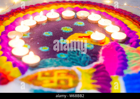 Beautiful rangoli made from colored powders and decorated with wax candle diyas on diwali eve. These patterns are hand made by the hindus and decorate