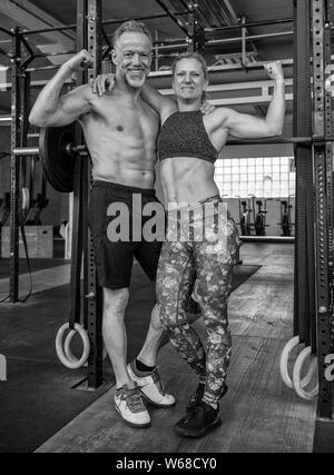 Portrait of a middle aged attractive and athletic couple who is showing their muscles and having fun. Strong man and woman in a gym. Black and white. - Stock Photo