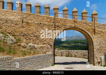 Open gate in a brick wall allows a beautiful view to a distant landscape of scattered houses in a forest, mountains and blue sky with clouds - Stock Photo