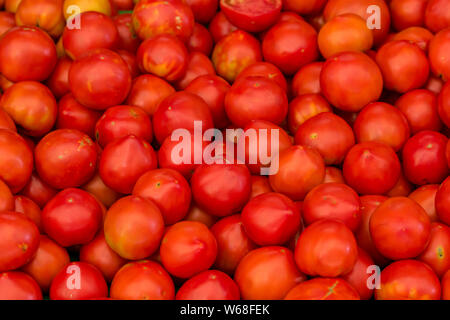 fresh tomatoes on a fruit and vegetable stand at a marketplace - Stock Photo