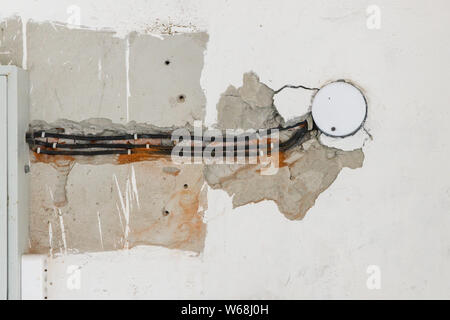 Several electrical cables are routed in the damaged wall - Stock Photo