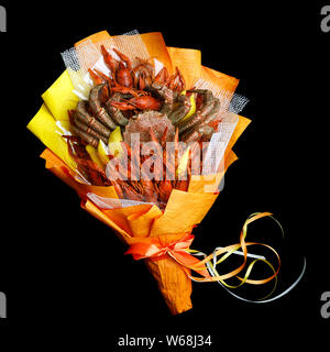Unique bouquet consisting of large crab and boiled crawfish wrapped in orange paper on a black background - Stock Photo