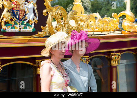Two women wearing hats standing beside Gloriana the Queen's golden barge on the riverbank at Henley Royal Regatta, Henley-on-Thames, England, UK - Stock Photo