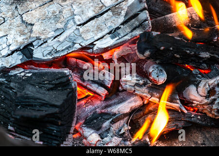Closeup of burning and smoldering firewood. Close-up of Burning coal. Glowing embers smoldering in the fireplace. Burning log of wood close-up as abst - Stock Photo