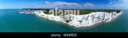 Aerial panorama of Port of Dover with ferry ships docked in passengers terminal and view over white cliffs, coastal countryside on a sunny summer day, - Stock Photo