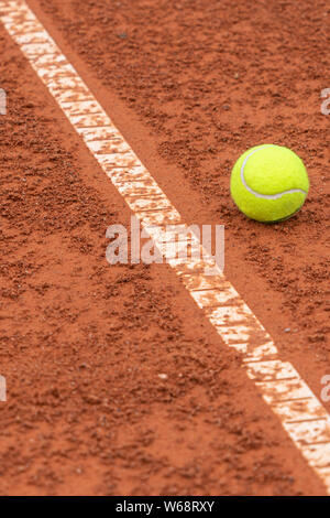 Tennis ball lying near white line on tennis court background - Stock Photo