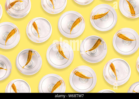 Aquarium fish. Fish in glass goblets on a yellow background. Goldfish swim in the water. Selling and buying fish. Art gallery, creative