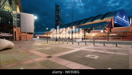 Long exposure at night of tram passing in Lower Mosley Street with Manchester Central, Bridgewater Hall and Beetham Tower in the background - Stock Photo